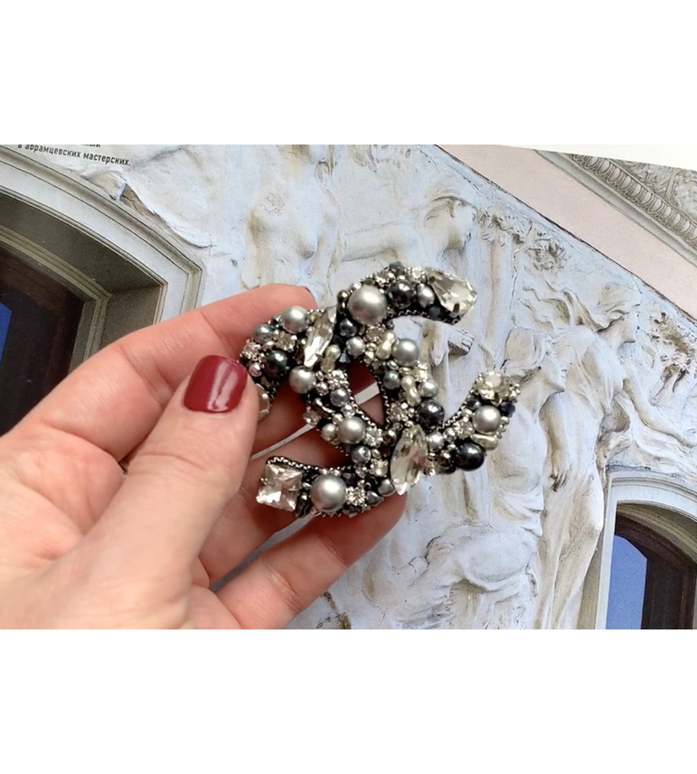Gray and black logo brooch